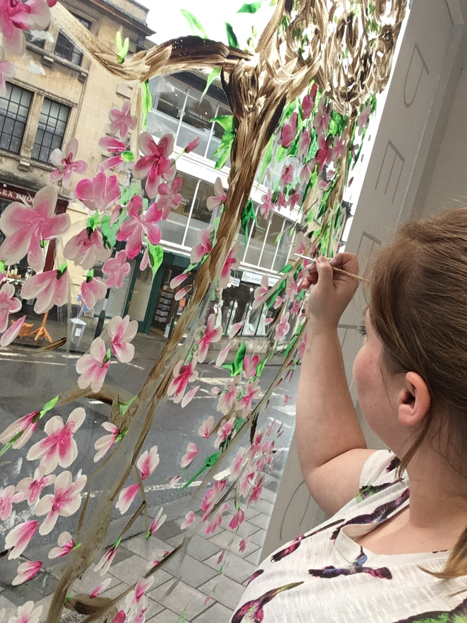 Cheryl hand painting cherry blossoms on a bridal shops window display in Bath.